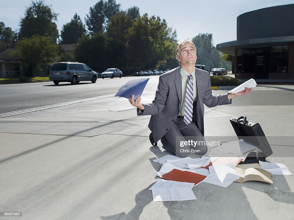 Businessman dropping papers from briefcase : Stock Photo
