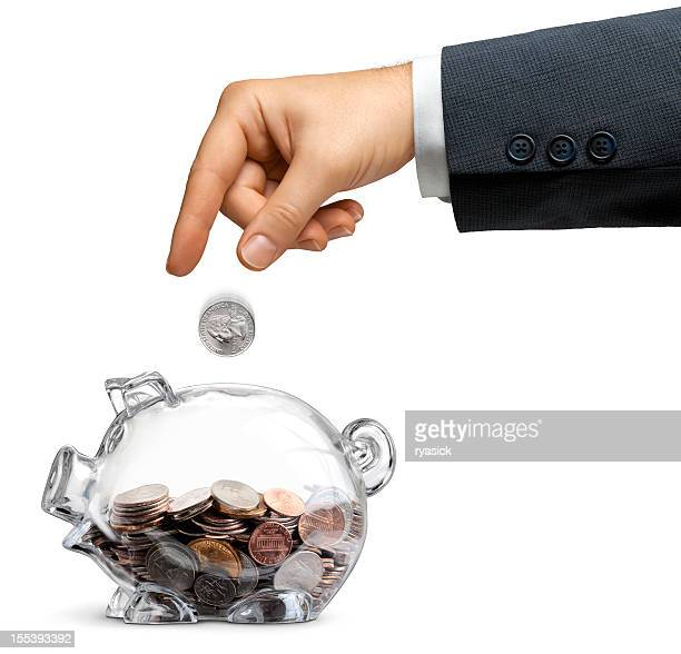 Businessman Drops Money Into A Half-filled Clear Piggy Bank Isolated