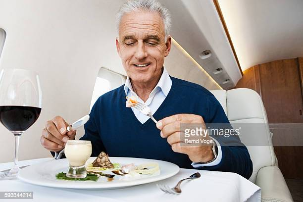 Businessman eating a meal on an airplane