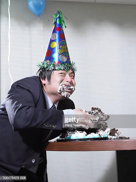 businessman eating birthday cake with hands, stuffing face - hans neleman ストックフォトと画像
