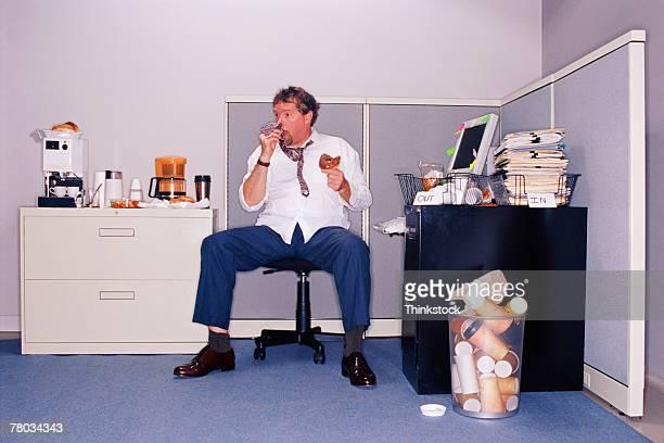 Businessman eating donuts at messy desk