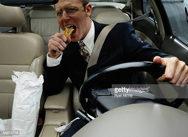 businessman eating french fries while driving - domestic car stock pictures, royalty-free photos & images