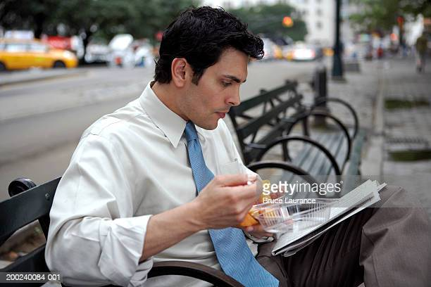 Businessman eating fruit on park bench, reading newspaper, side view
