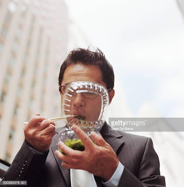 Businessman eating greens, using chopsticks