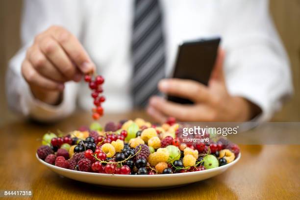 businessman eating healthy food during work, summer berry fruits on white plate - unhealthy living stock pictures, royalty-free photos & images