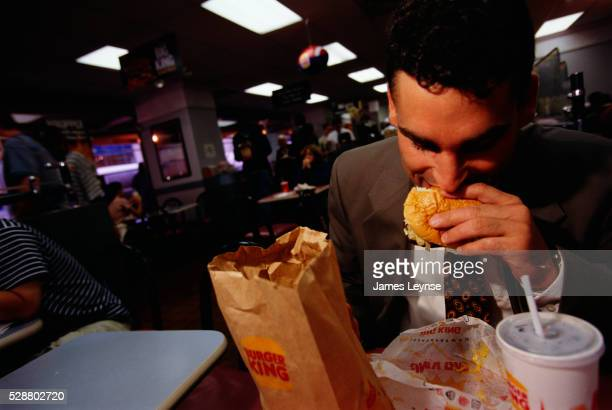 businessman eating lunch at burger king - burger king stock pictures, royalty-free photos & images