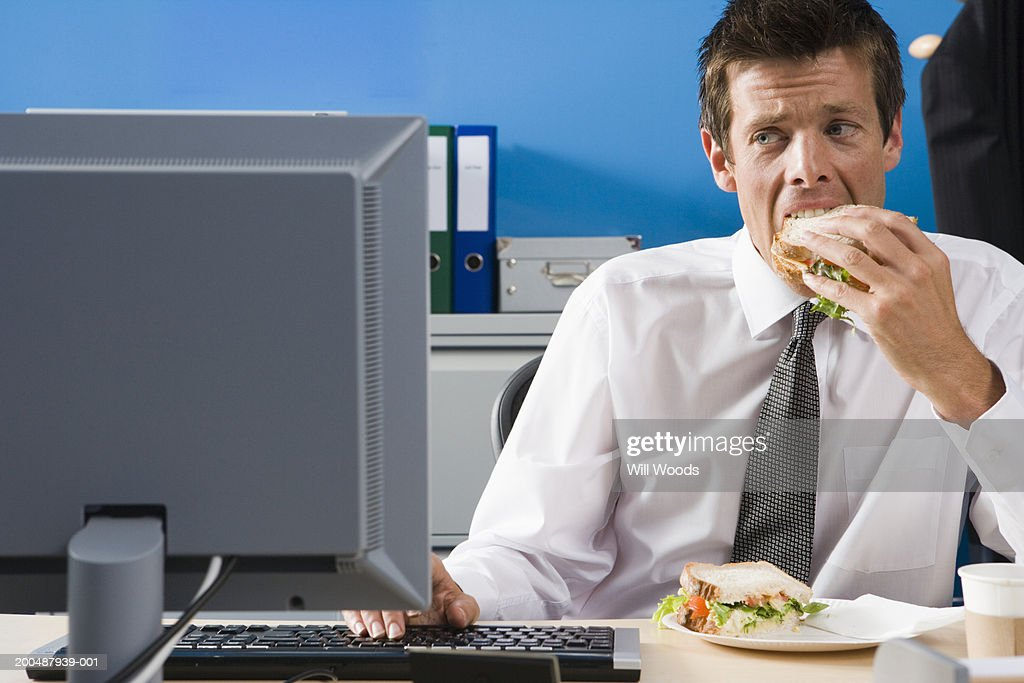 Businessman eating lunch at desk : Stock Photo