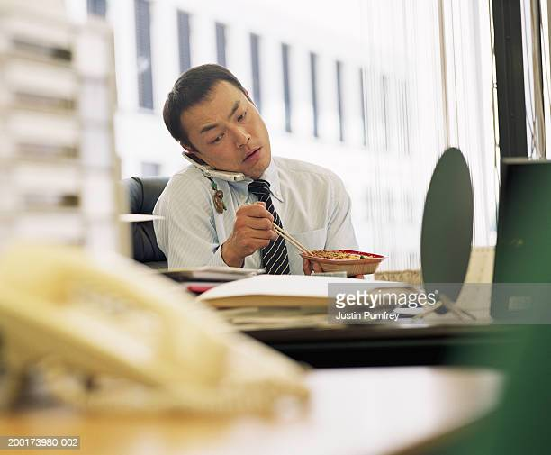 Businessman eating lunch at desk, using mobile phone