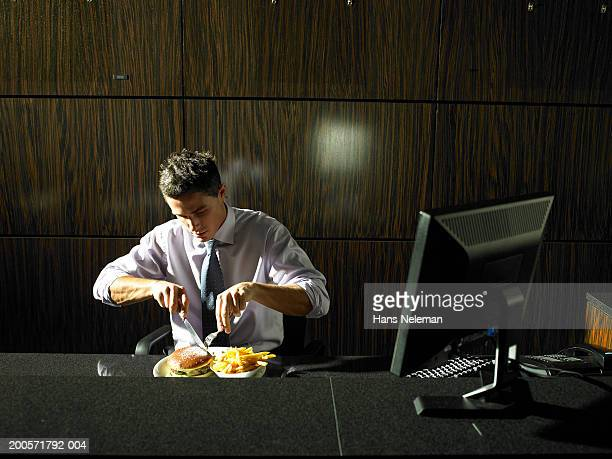Businessman eating meal at desk, night