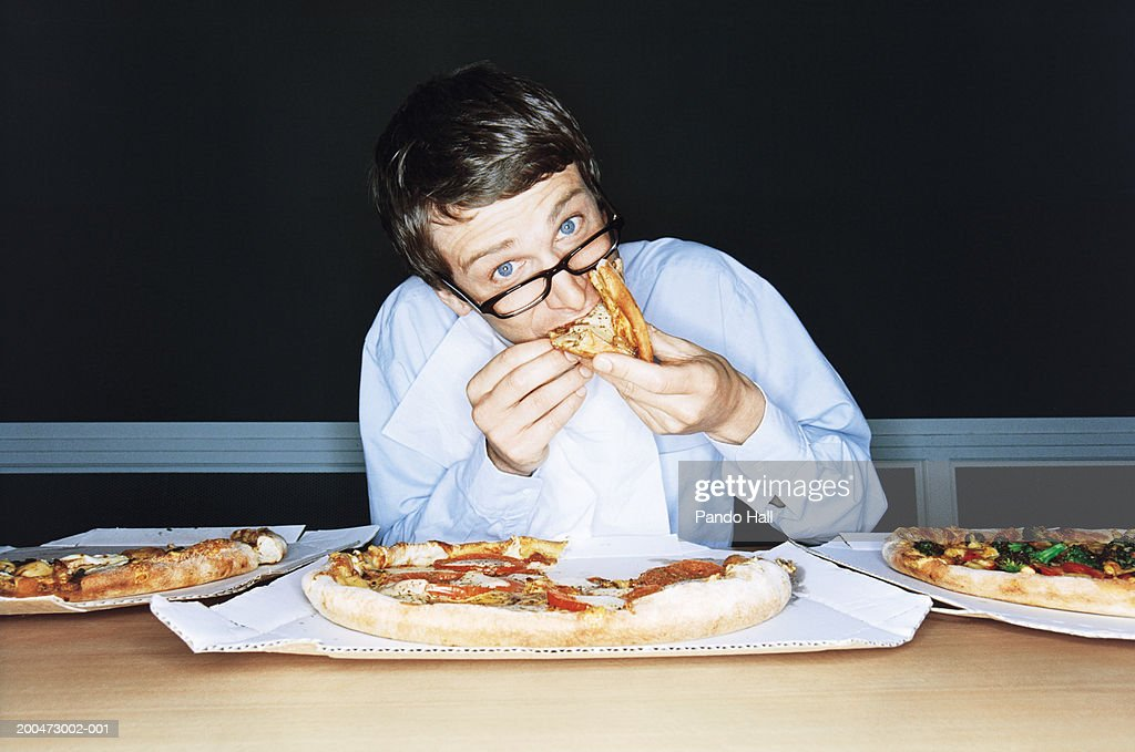 Businessman eating pizza from boxes on table, portrait : Stock Photo