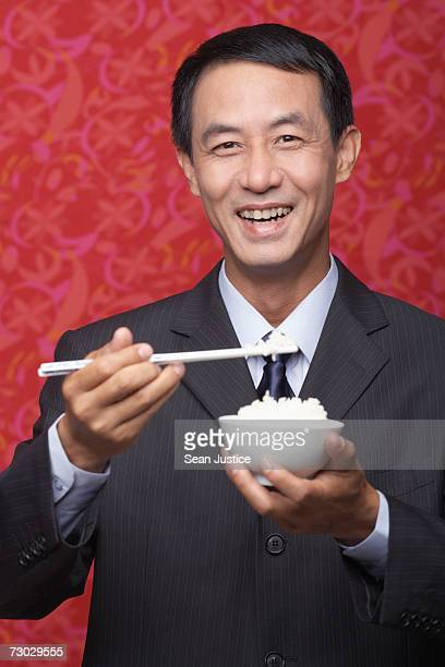 Businessman eating rice, portrait
