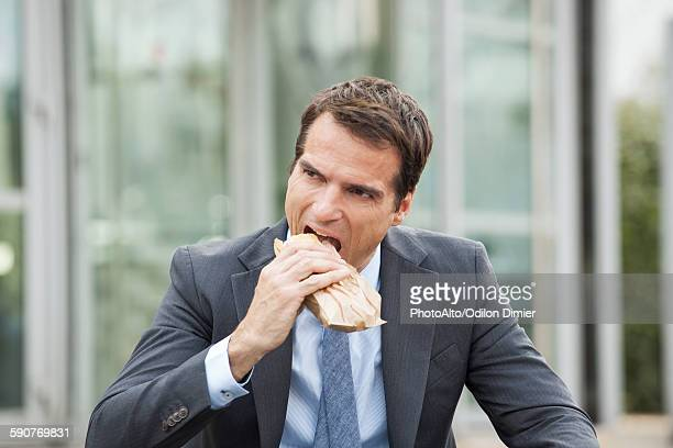 Businessman eating sandwich outdoors