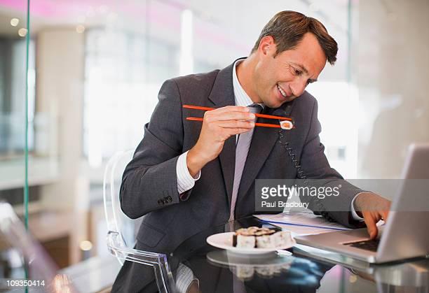 Geschäftsmann Essen sushi und spricht am Telefon