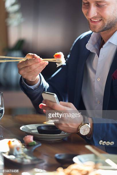 Businessman eating sushi and text messaging