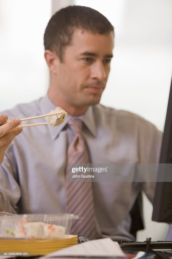 Businessman eating sushi at desk looking at computer : Foto stock
