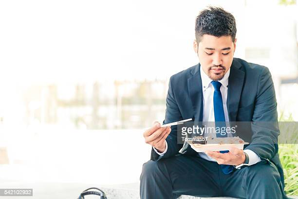 businessman eating sushi outdoor
