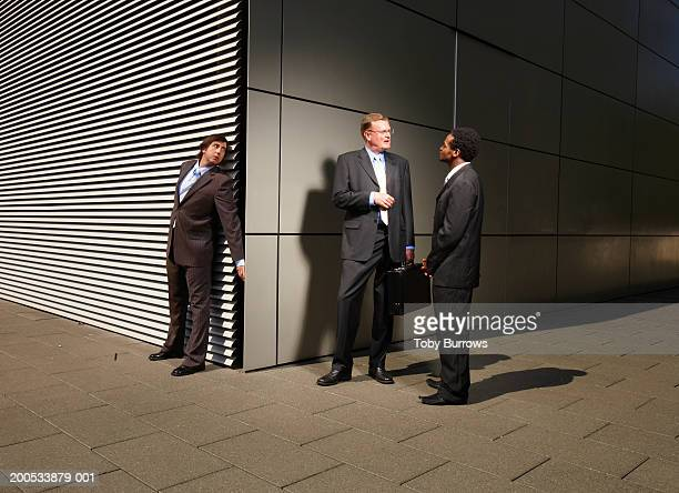 Businessman eavesdropping on conversation at street corner