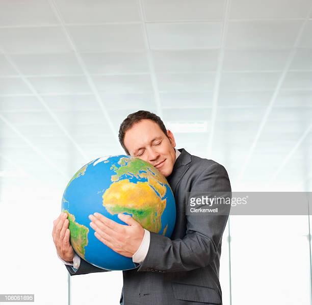 Empresario adoptando un mundo, los ojos cerrados