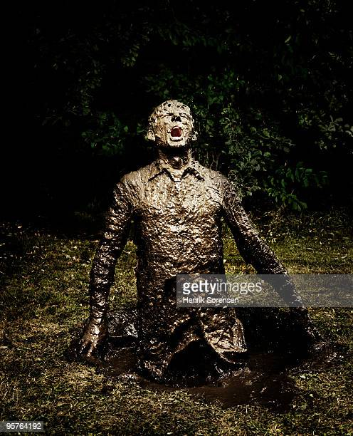 Businessman emerging from a mud hole