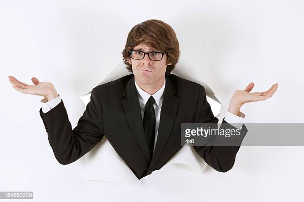 businessman emerging through hole in paper and making face - caucasian appearance stock pictures, royalty-free photos & images