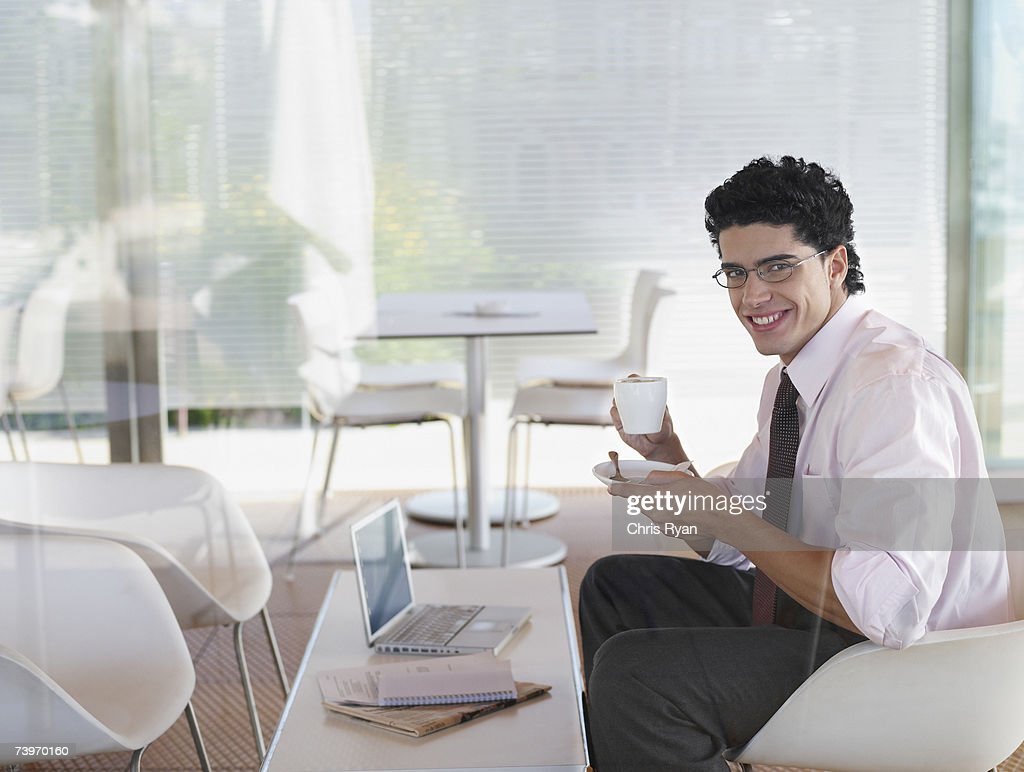 Businessman enjoying a cup of coffee in a cafe : Stock Photo
