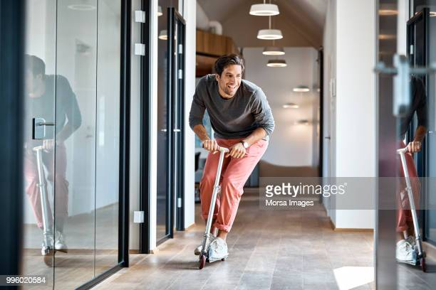 businessman enjoying on push scooter in office - fun stock pictures, royalty-free photos & images