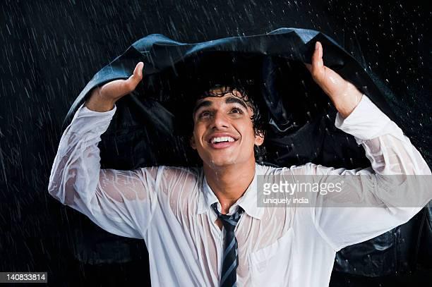 Businessman enjoying the rain