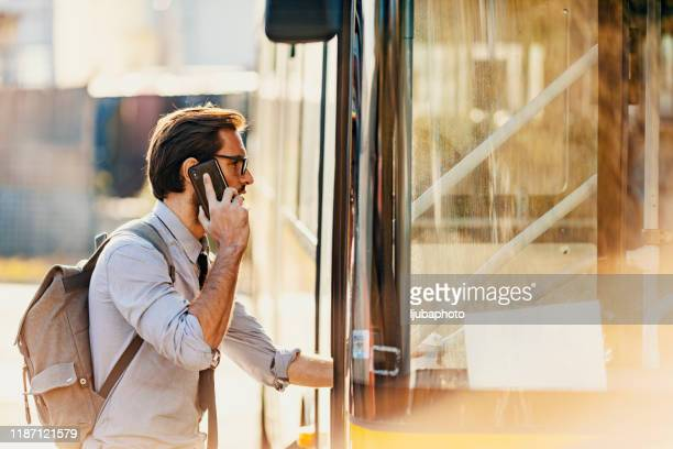 businessman entering a bus - entering stock pictures, royalty-free photos & images