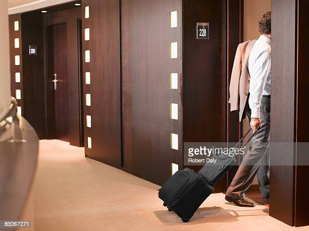Businessman entering hotel room with suitcase