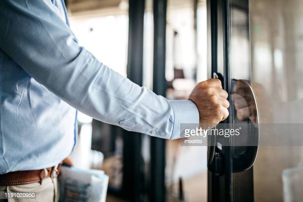 businessman entering office cabin - entrata foto e immagini stock