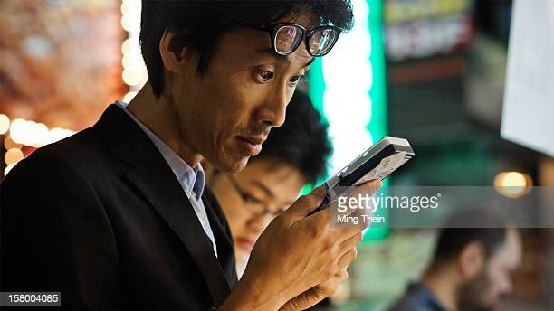 Businessman examines an electronics toolkit after work at night at a streetfront vendor in Akihabara Tokyo