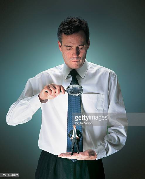 Businessman Examining a Smaller Man Standing on his Palm Through a Magnifying Glass