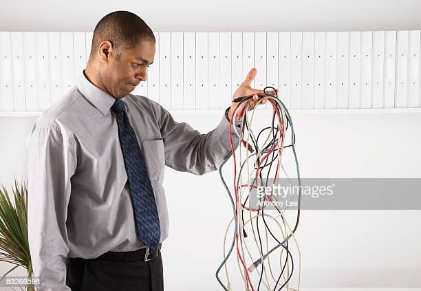 businessman examining a tangle of electronic cords - ケーブル線 ストックフォトと画像