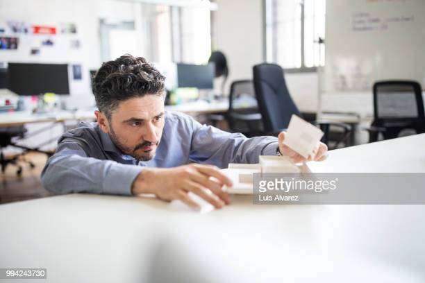 businessman examining architectural model on desk - concentration stock pictures, royalty-free photos & images