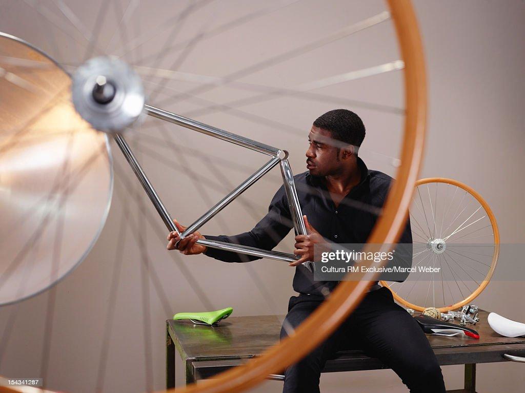 Businessman examining bicycle part : Stock Photo