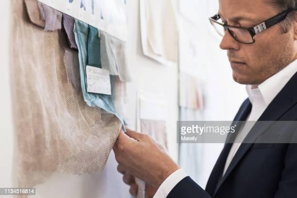 businessman examining fabric swatches - überprüfung stock-fotos und bilder
