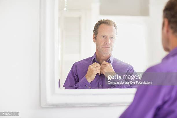 businessman examining himself in mirror - purple shirt stock photos and pictures