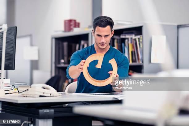 ビジネスマンのオフィスでの机でモデルの検討