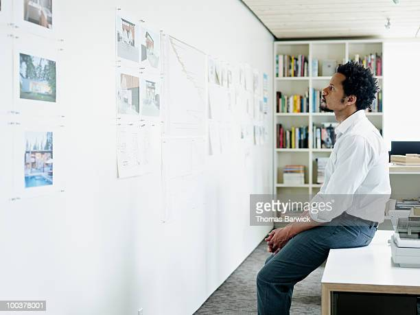 Businessman examining plans on wall of office