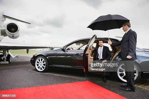 Businessman exiting limousine on airport runway