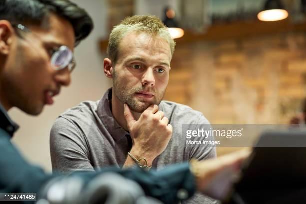 businessman explaining colleague during meeting - nouvelle entreprise photos et images de collection