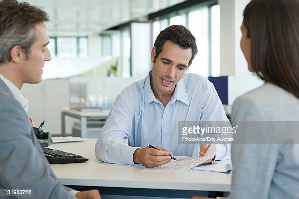 Businessman explaining document to clients