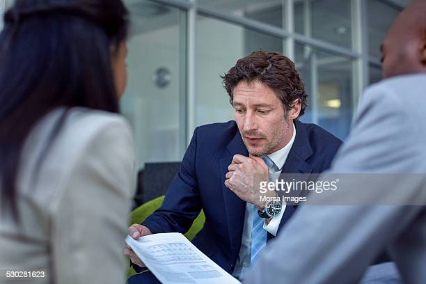 Businessman explaining documents to colleagues