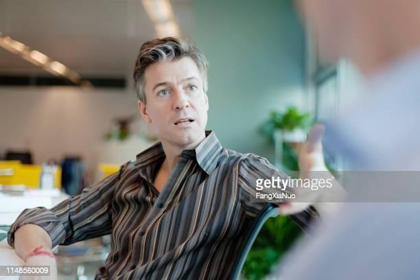 オフィスで同僚にアイデアを説明するビジネスマン - コミュニケーション不足 ストックフォトと画像