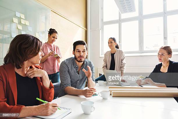Businessman explaining new project to female colleagues at conference table