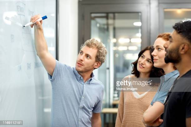 businessman explaining plan to coworkers in office - differing abilities female business fotografías e imágenes de stock