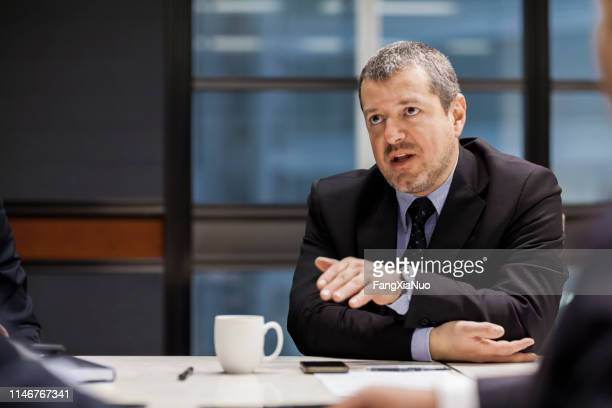 businessman explaining positioning in meeting - talking politics stock pictures, royalty-free photos & images