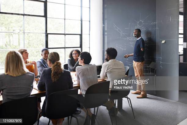 businessman explaining to coworkers in meeting - disabilitycollection stock-fotos und bilder