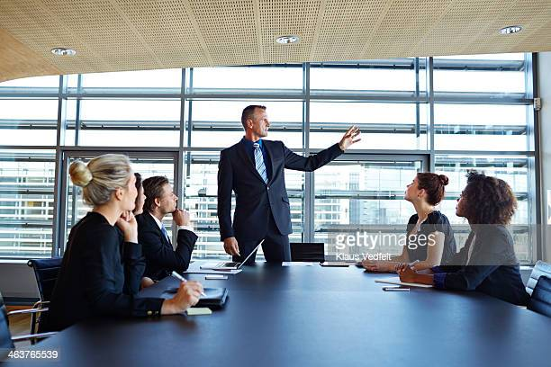 businessman explaining to coworkers - formal stock pictures, royalty-free photos & images