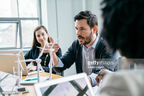 businessman explaining wind turbine models to colleagues in office - environmentalist stock pictures, royalty-free photos & images